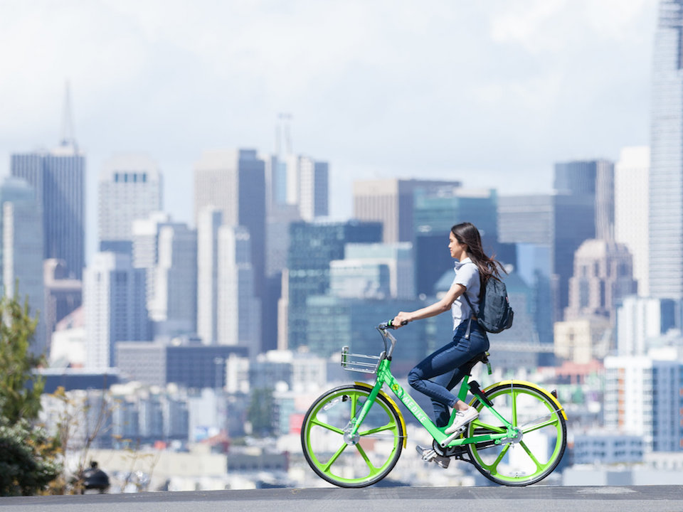 A woman rides a limebike against the sf skyline